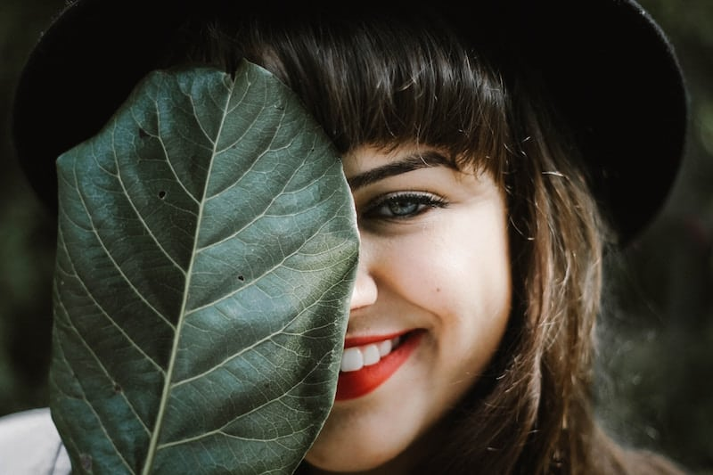 woman smiling behind a large leaf