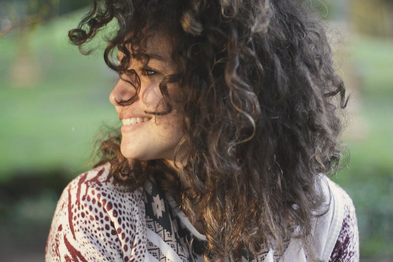 woman with curly dark hair smiling