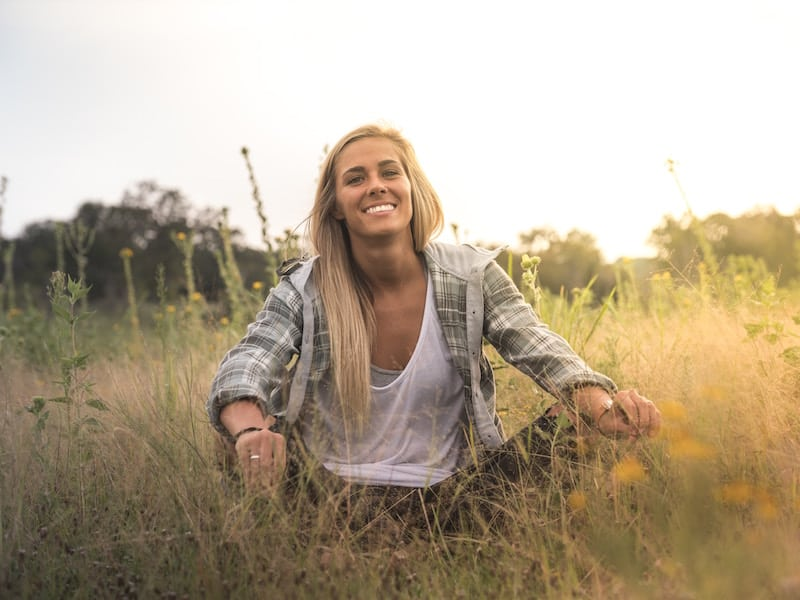 woman sitting in a grassy field smiling